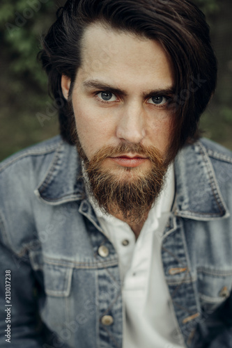 Photo A large-sized portrait of a bearded dark-haired guy in a blue jeans similar to