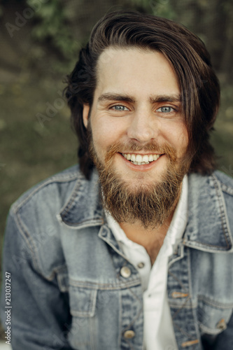 A large-sized portrait of a bearded dark-haired guy in a blue jeans similar to Wallpaper Mural