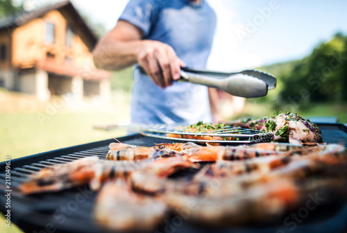 Foto Unrecognizable man cooking seafood on a barbecue grill in the backyard