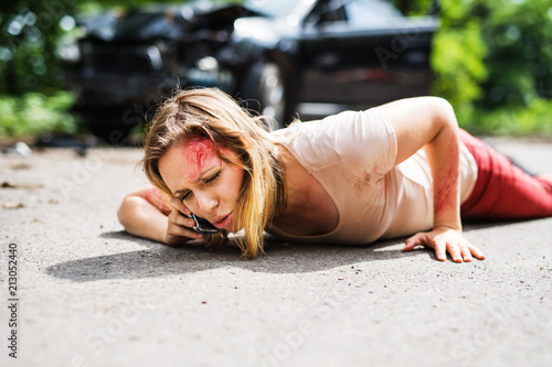 Fototapeta Young injured woman lying on the road after a car accident, making a phone call. obraz na płótnie