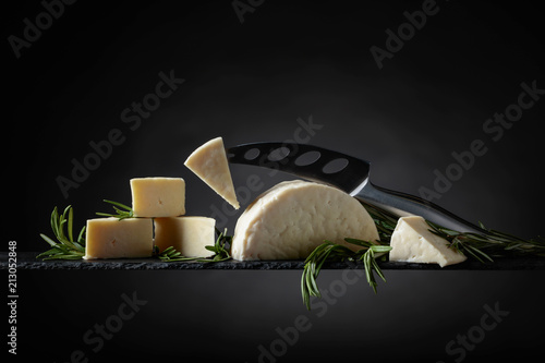 Fototapeta Sheep cheese with rosemary on a black background. obraz
