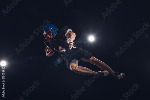 Fotografiet  bottom view of american football player jumping with ball under spotlights on bl
