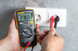 Electrician checking voltage in socket