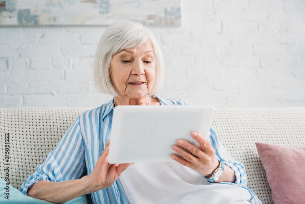 Fototapeta portrait of senior woman using tablet on sofa at home