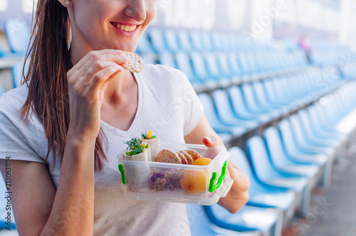 Papiers peints Assortiment Young woman eating from lunch box in stadium