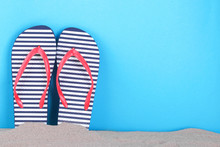 Flip Flops In A White And Blue Strip In The Sand On A Blue Background With A Place For An Inscription