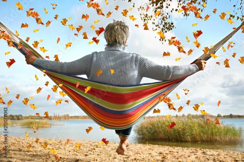 Leinwand Poster Seniorin am See im Herbst