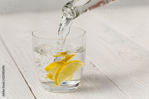 Fotografia  Pouring water from a glass bottle into a glass with lemon slices