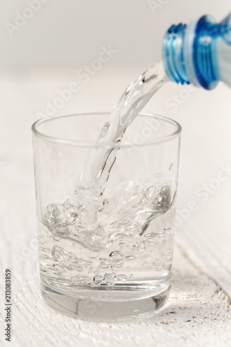 Fotografia  Pouring water from a plastic bottle into a glass