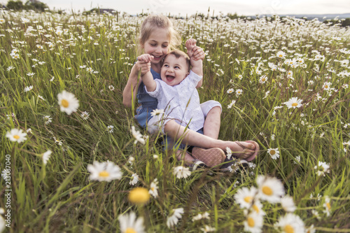 Photo  Cute child girl at camomile field daisy with baby brother