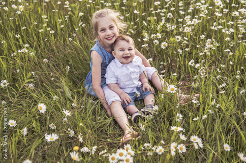Cute child girl at camomile field daisy with baby brother Canvas Print