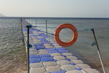 Closed With Red Lifebuoy And Ropes Passage To Swimming Area On Summer Tropical Beach. Horizontal Color Photography.