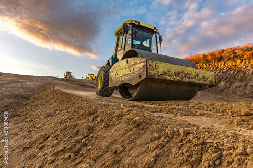Yellow steamroller on road in sunlight