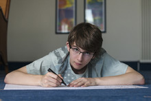 Young Student Teenager In Glasses Lies On The Floor And Then Writes A Felt-tip Pen On Paper.