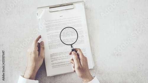 Valokuva  Man hands looking document with magnifying glass