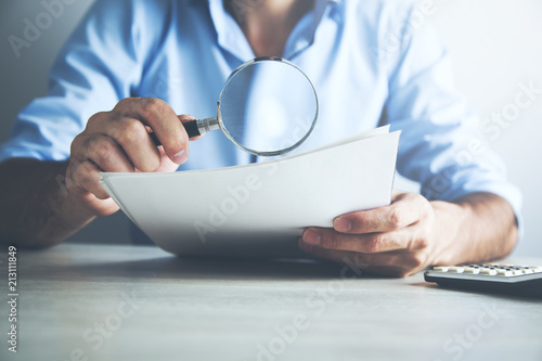 Fotomural  Businessman looking through a magnifying glass to documents