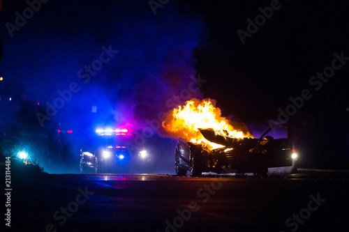 Photo Car on fire at night with police lights in background