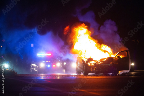 Car on fire at night with police lights in background