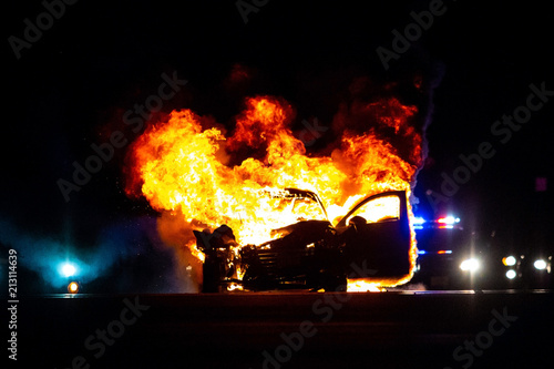 Car on fire at night with police lights in background Wallpaper Mural