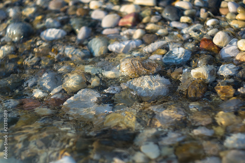 Aluminium Prints Forest river pebble stones on the sea beach, the rolling waves of the sea with foam