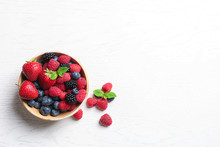 Bowl With Raspberries And Different Berries On Wooden Table, Top View