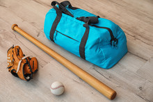 Sports Bag, Baseball Ball And Bat On Wooden Floor