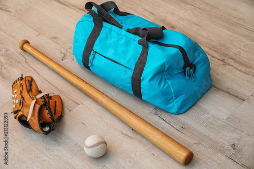 Fotografía Sports bag, baseball ball and bat on wooden floor