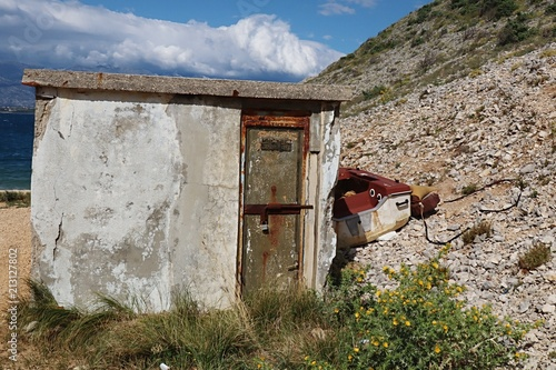 In de dag Poort Small concrete fisherman shed with peeling plasterwork and rusty doors with laminate fishing boat placed behind. Located in small rocky bay in Croatia, Adriatic
