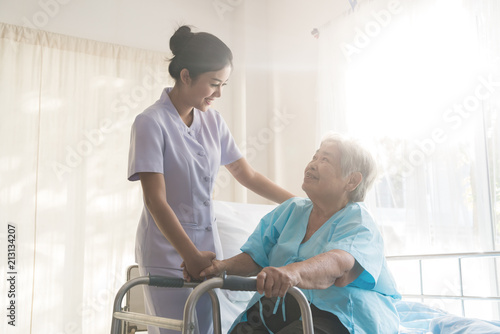 Asian young nurse supporting elderly patient disabled woman in using walker in hospital. Elderly patient care concept..