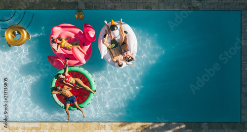Friends relaxing on inflatable mattresses in pool Fototapeta
