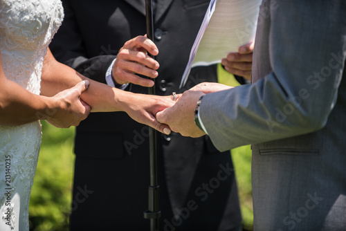 Photo Groom slides diamond ring onto his bride's finger as official looks on during wedding ceremony at alter
