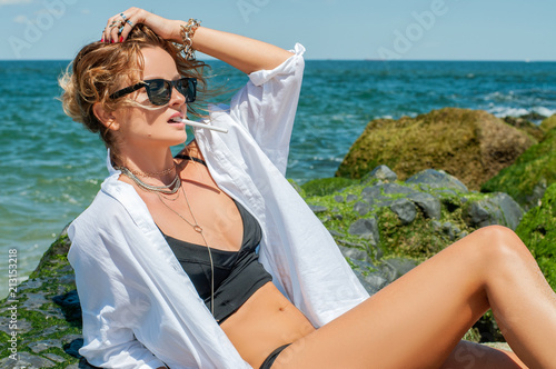 Beautiful fashion woman is smoking on the beach