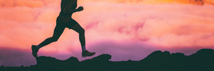 Trail runner legs of man athlete running on rocks in sky pink clouds background. Panoramic banner silhouette of run workout fitness concept.