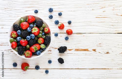 Fotografía Fresh juicy ripe berries in a white plate-strawberries, blueberries, blackberrie