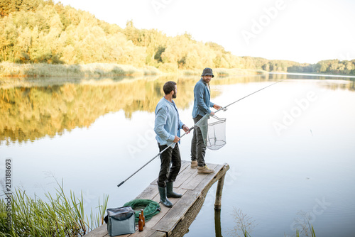 Fotobehang Vissen Two male friends preparing for fishing standing with fishing net and rod on the wooden pier during the morning light on the lake
