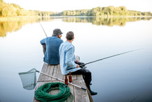 Two Male Friends Dressed In Blue Shirts Fishing Together With Net And Rod Sitting On The Wooden Pier During The Morning Light On The Lake