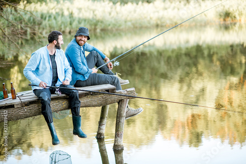 Canvas Prints Fishing Two male friends dressed in blue shirts fishing together with net and rod sitting on the wooden pier during the morning light on the lake