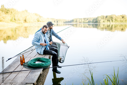 Poster Peche Two friends catching fish with fishing net and rod sitting on the wooden pier at the lake