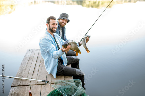 Printed kitchen splashbacks Fishing Two happy fishermen holding caught fish sitting on the wooden pier during the fishing on the lake at the morning