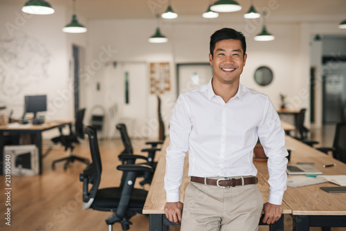 Foto Smiling Asian businessman leaning on a table in an office