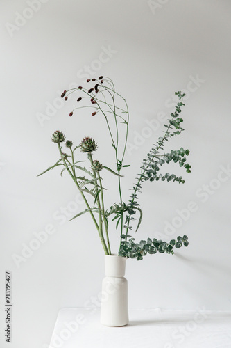 Fotobehang Bloemen A floral arrangement in a beige vase in a clean white setting, containing eucalyptus, artichoke, great burnet catching the summer evening light.