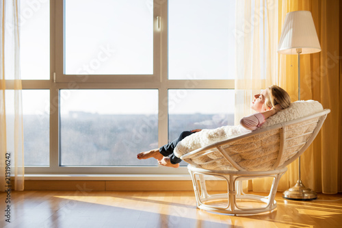 Obraz Woman relaxing in chair by the window - fototapety do salonu