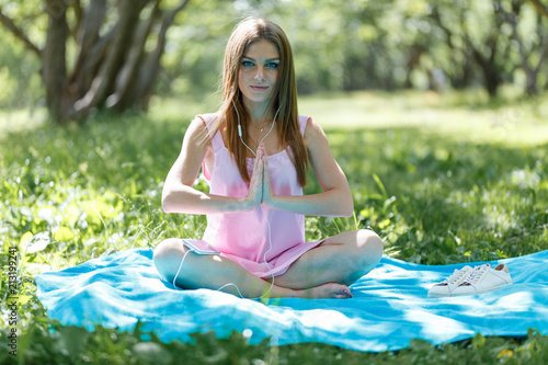Woman meditating on green grass at the park sitting in lotus position. Fitness girl relaxing in yoga pose after exercises