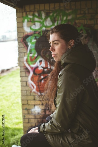 Woman relaxing against graffiti wall