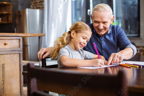 Nice little girl drawing with her grandfather