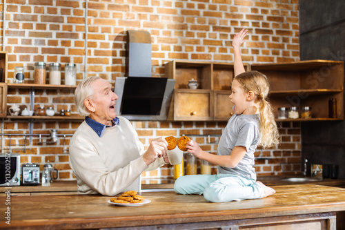 Fotografie, Obraz  Joyful aged man eating home made pastry with his granddaughter