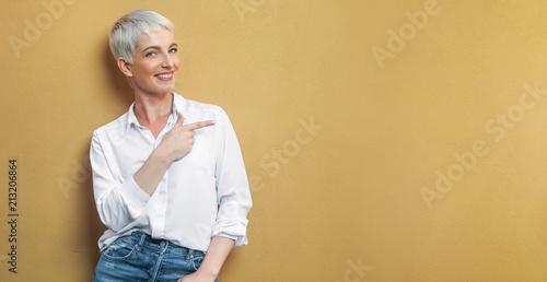 Fototapeta Frau an der Wand zeigt auf leere Fläche