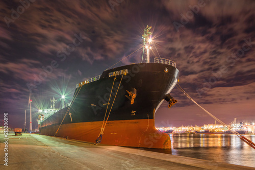 Foto  Massive moored oil tanker at night with a dramatic cloudy sky, Port of Antwerp, Belgium