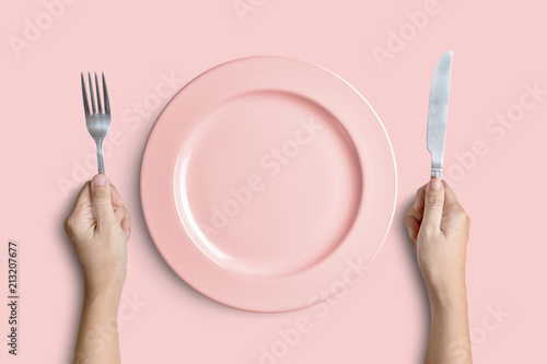 Obraz na plátně Pink plate with silver fork and knife on pink background with clipping path