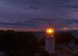 Lighthouse glowing at dark night on coast Spain